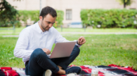 A man is working using laptop at park. Outdoor, guy look challenged and thinking.