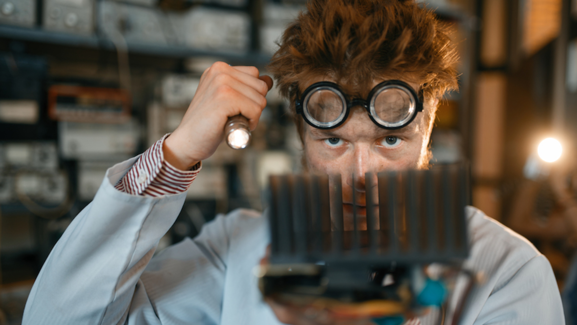 Strange engineer examines the cooling radiator, test in laboratory. Electrical testing tools on background. Lab equipment, engineering workshop