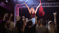 Female performer with  arms raised singing during music event at nightclub